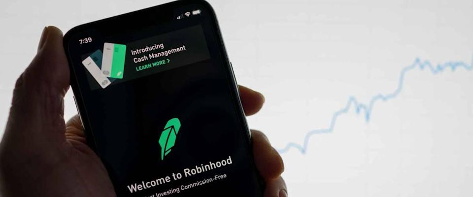 Robinhood app on phone with white financial stock chart with price rising upward positive in background