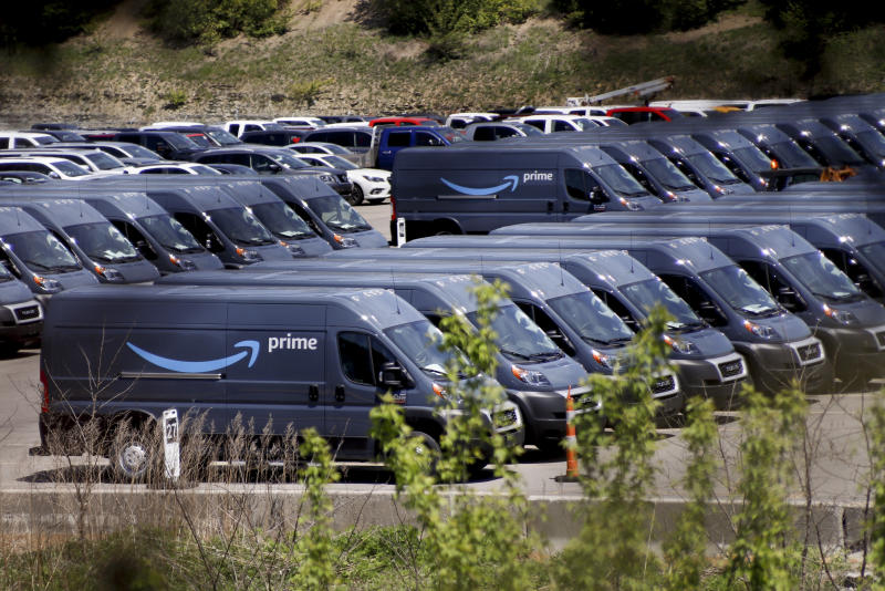 Rows of Amazon Prime delivery vans are stored in the lots at the Cox Automotive Inc. Manheim Pittsburgh vehicle auctioning location in Cranberry Township, Pa., Wednesday, May 13, 2020. The corporation announced earlier this week it will furlough hundreds of workers here and more at it's other locations around the country due to the COVID-19 pandemic. (AP Photo/Keith Srakocic)