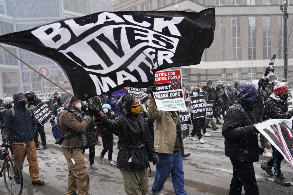 A group of protesters march in the snow around the Hennepin County Government Center, Monday, March 15, 2021, in Minneapolis where the second week of jury selection continues in the trial for former Minneapolis police officer Derek Chauvin. Chauvin is charged with murder in the death of George Floyd during an arrest last may in Minneapolis. (AP Photo/Jim Mone)