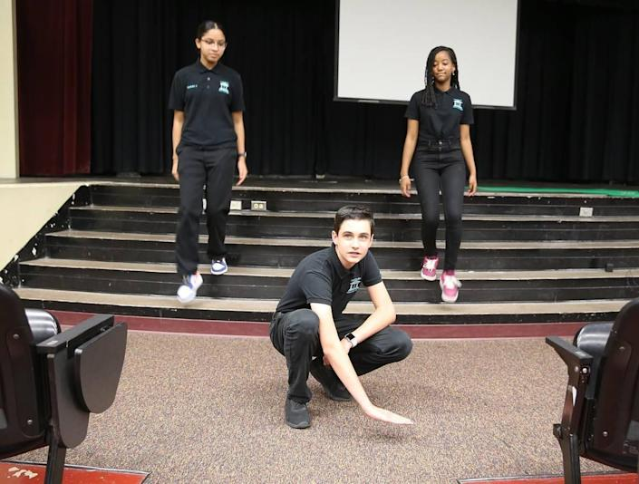 Maurits Acosta shows the level of the water in the auditorium after a storm as Jocelyn Hernandez and Gabriella Vega descend the stairs on June 9, 2021. Miami Lakes Middle School students have proposed flood prevention legislation to the town council after Tropical Storm Eta flooded parts of the west Miami-Dade town, including their school auditorium.