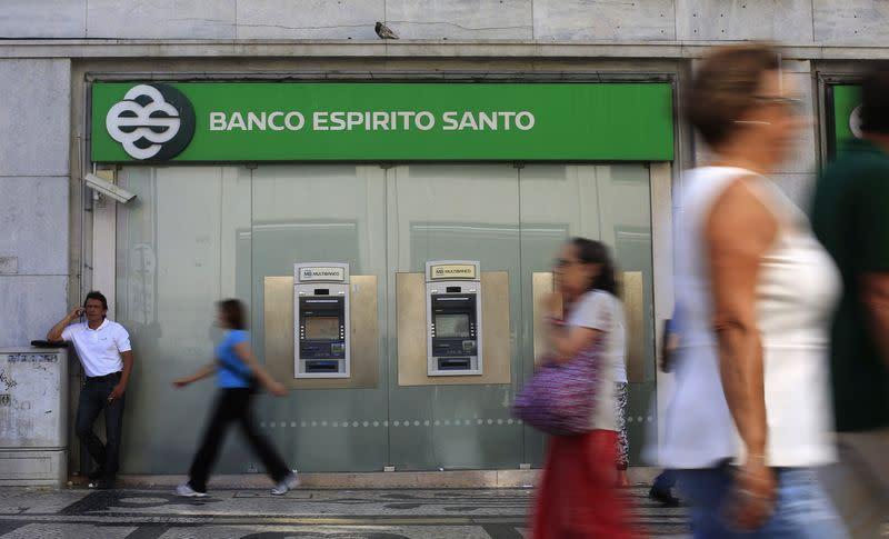 People walk past an office of Portuguese bank BES in downtown Lisbon