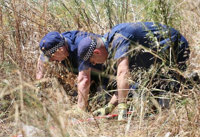 British police conduct a finger-tip search in 2014 of an area of scrubland close to where Madeleine McCann went missing
