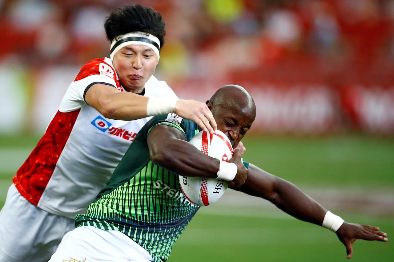 Rugby Union - Singapore Sevens - National Stadium, Singapore - 15/04/17 South Africa's Sandile Ngcobo (R) attempts to evade a tackle by Japan's Jonmoon Han. REUTERS/Yong Teck Lim
