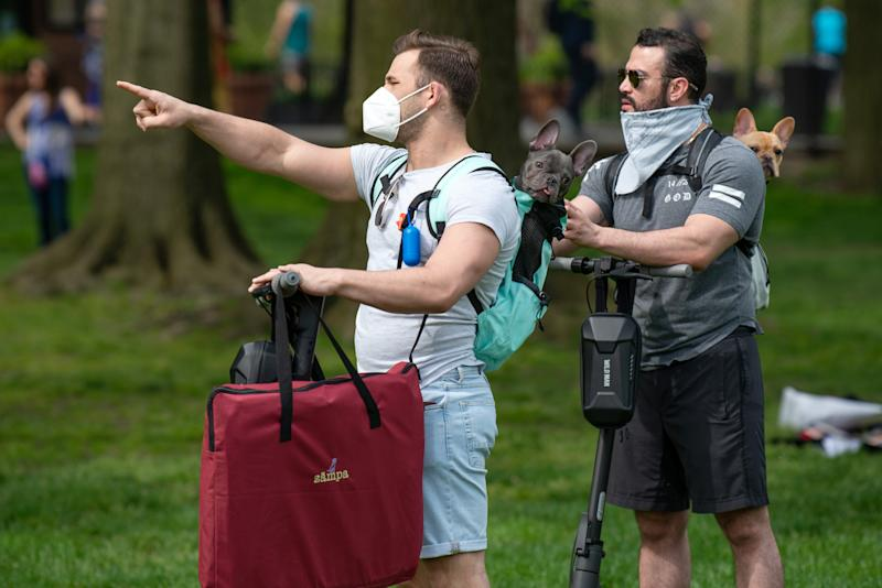 Two people wearing masks carry their dogs in their backpack through Sheep Meadow, Central Park as temperatures rose amid the coronavirus pandemic on May 2, 2020 in New York City. (Photo: Alexi Rosenfeld/Getty Images)