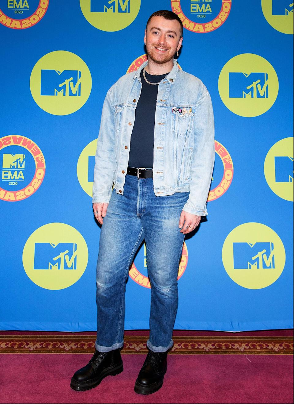 <p>Sam Smith wears a lightwash denim jacket with mid-indigo jeans, a black shirt, and black boots.</p>