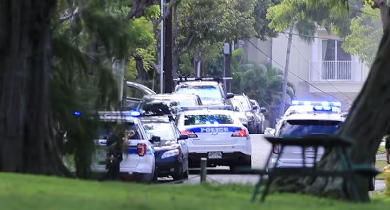 Police cars at the scene of Hawaii shooting where two officers were shot and homes on fire.