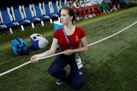 A volunteer holds a rope to prevent photographers entering the bench area before the 2018 FIFA World Cup soccer match between Switzerland and Costa Rica at Nizhny Novgorod Stadium in Nizhny Novgorod, Russia June 27, 2018. REUTERS/Murad Sezer
