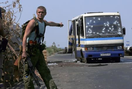 An armed pro-Russian separatist points at a bus riddled with bullet holes at a checkpoint on the outskirts of Donetsk