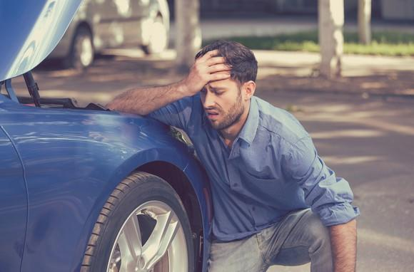 Man crouching next to car with hood up, looking frustrated.
