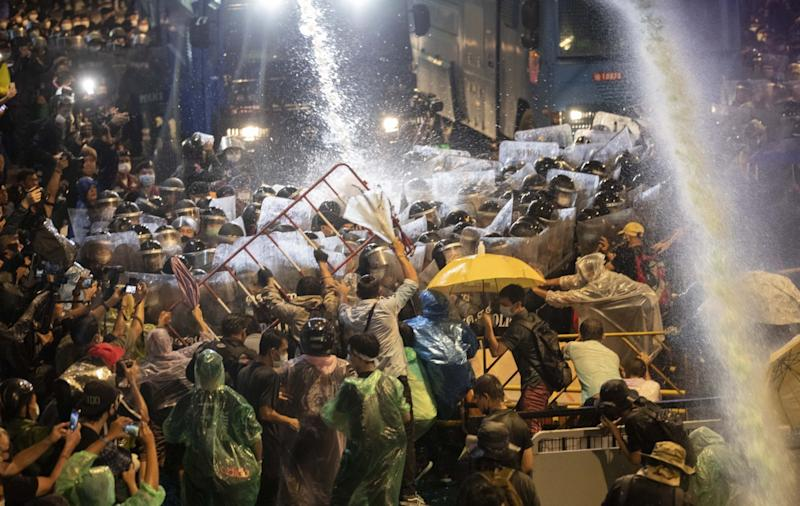 A phalanx of police in riot gear with shields pushes against protesters as water cannons douse them