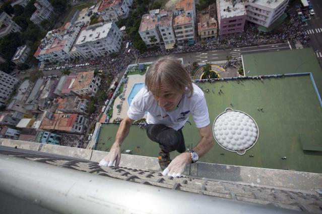 French daredevil Alain Robert scales the Habana Libre hotel without using ropes or a safety net, in Havana, Cuba, Monday, Feb. 4, 2013. Once the city's Hilton, Robert was able to reach the top of the 27-story building in 30 minutes. Robert has scaled much taller buildings in his career. He says his main concern is that the hotel is in disrepair like other Havana landmarks. (AP Photo/Ramon Espinosa, Pool)