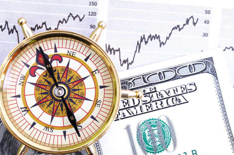 Compass and US dollars on financial page.