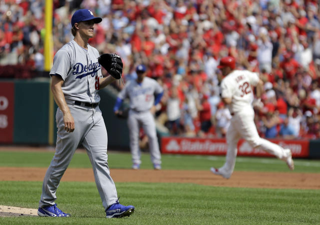 St. Louis Cardinals' Matt Adams, right, rounds the bases after hitting a two-run home run off Los Angeles Dodgers starting pitcher Zack Greinke, left, during the first inning of a baseball game Saturday, July 19, 2014, in St. Louis. (AP Photo/Jeff Roberson)
