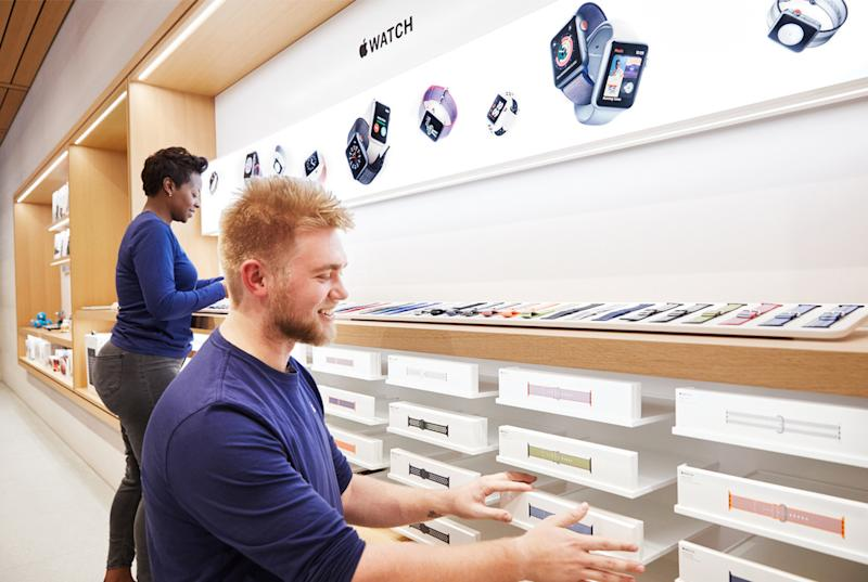 Apple Store employees stocking shevles with Apple Watch bands