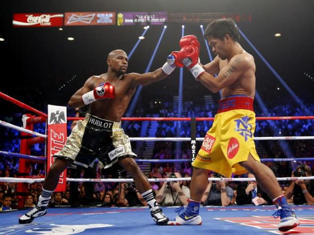 Mayweather, Jr. of the U.S. and Pacquiao of the Philippines fight in the first round of their welterweight WBO, WBC and WBA (Super) title fight in Las Vegas