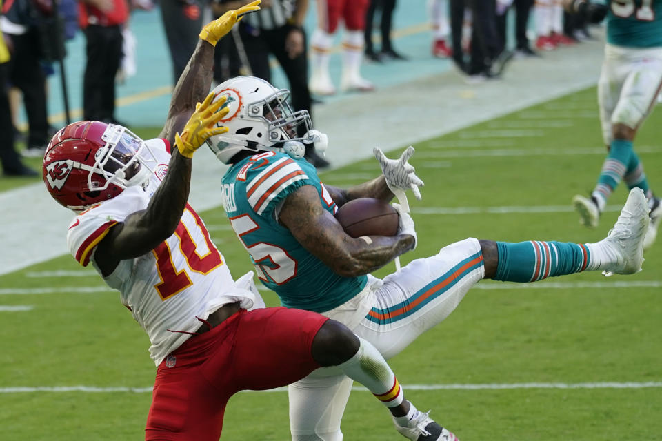 FILE - Miami Dolphins cornerback Xavien Howard (25) intercepts a pass intended for Kansas City Chiefs wide receiver Tyreek Hill (10), during the second half of an NFL football game in Miami Gardens, Fla., in this Sunday, Dec. 13, 2020, file photo. All-Pro cornerback Xavien Howard joined the rest of the Miami Dolphins reporting for training camp Tuesday, July 27, 2021, after he sat out mandatory minicamp because he's unhappy about his contract. (AP Photo/Lynne Sladky, File)
