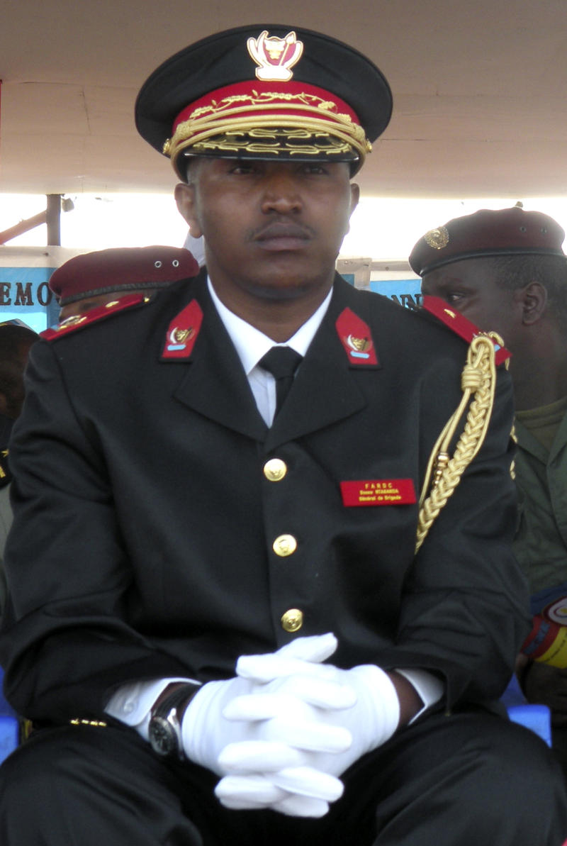 FILE - In this June 30, 2010 file photo, Congolese former  warlord Bosco Ntaganda in his national army uniform attends the 50th anniversary celebration of Congo's independence in Goma in eastern Congo.   The notorious ex-warlord who became a general in the Congolese army even as the International Criminal Court sought him on war crimes charges is being blamed for fomenting even more unrest in the Congo and faces new charges of crimes against humanity. The Congolese military is hunting for Bosco Ntaganda, whose loyalists have split off from the military and formed a new rebel group  in the wilds of eastern Congo. (AP Photo/T.J. Kirkpatrick, File)