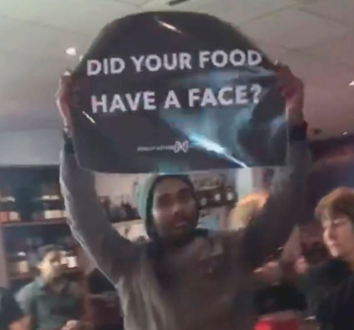 """Pictured is a protester holding a sign inside the Lapa Brazilian BBQ restaurant that asks, """"Did your food have a face?"""""""