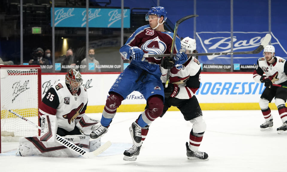 Colorado Avalanche left wing Andre Burakovsky, center, jumps as the puck sails into Arizona Coyotes goaltender Darcy Kuemper and Coyotes defenseman Jason Demers fights for position in front of the net in the first period of an NHL hockey game Monday, March 8, 2021, in downtown Denver. (AP Photo/David Zalubowski)