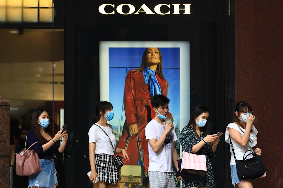 SINGAPORE - JUNE 20:  Shoppers wearing protective masks walk past a COACH boutique at Orchard Road on June 20, 2020 in Singapore. From June 19, Singapore started to further ease the coronavirus (COVID-19) restrictions by allowing social gatherings up to five people, re-opening of retail outlets and dining in at food and beverage outlets, subjected to safe distancing. Parks, beaches, sports amenities and public facilities in the housing estates will also reopen. However, large scale events, religious congregations, libraries, galleries and theatres will remain closed.  (Photo by Suhaimi Abdullah/Getty Images)