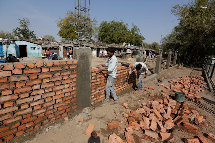 Workers construct a wall in front of a slum ahead of President Donald Trump's visit, in Ahmadabad, India. (Photo: ASSOCIATED PRESS)