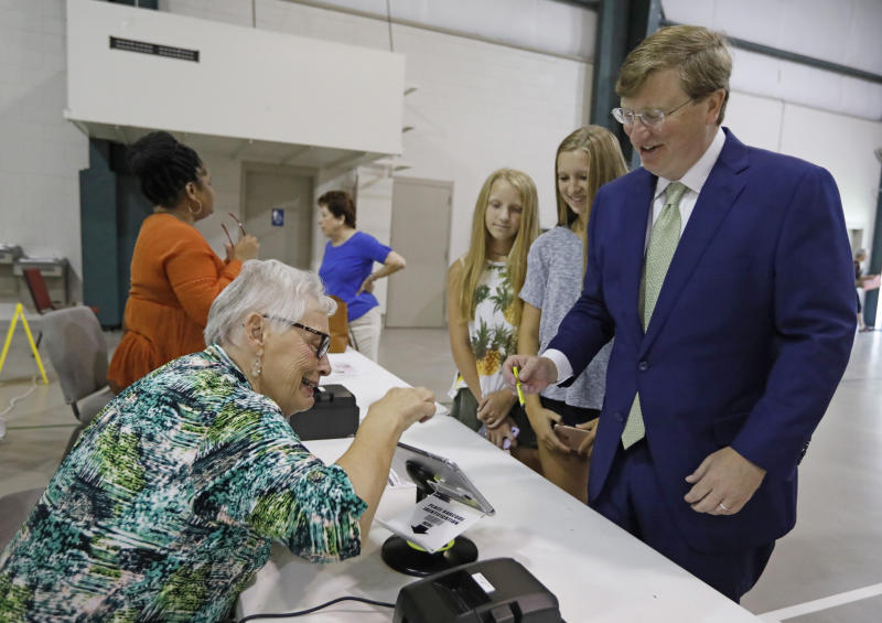 Republican poll worker Glenda McHenry, left, jokes about the legibility of Lt. Gov. Tate Reeves signature, to his daughters Elizabeth Magee Reeves, second from left, and Sarah Tyler Reeves, second from right, as Reeves prepares to receive his ballot at a Flowood, Miss., precinct in the party primary, Tuesday, Aug. 6, 2019. Reeves is a gubernatorial candidate. (AP Photo/Rogelio V. Solis)