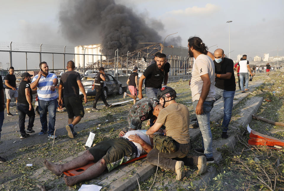 Rescue workers help an injured man at the explosion scene that hit the seaport of Beirut, Lebanon, Tuesday, Aug. 4, 2020. (AP Photo/Hussein Malla)