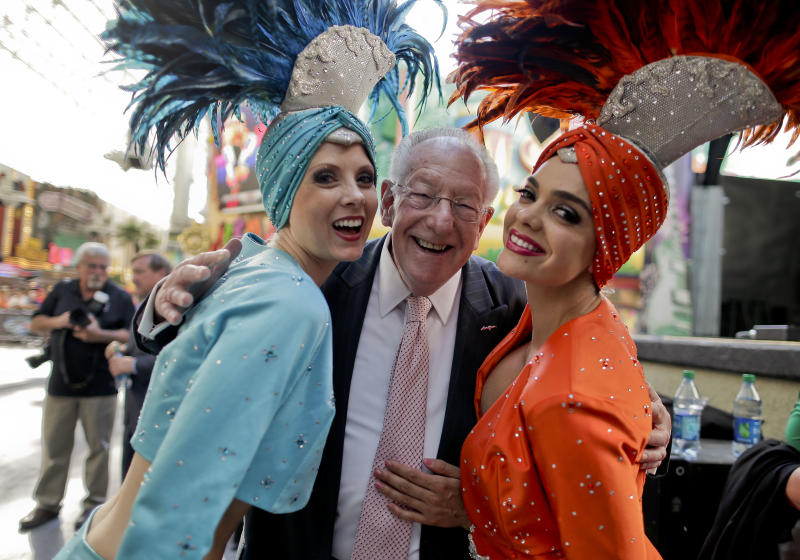 """Oscar Goodman poses for photos with two showgirls before kicking off a car show at the Fremont Street Experience, 105Friday, May 17, 2013, in Las Vegas. The former Las Vegas mayor branded the city with a larger than life persona. And now he's branded himself again with a memoir. In """"Being Oscar--From Mob Lawyer to Mayor of Las Vegas, Only in America,"""" Goodman tells all from his days as a lawyer representing members of the mob to his three terms as the """"happiest mayor in the universe."""" (AP Photo/Julie Jacobson)"""