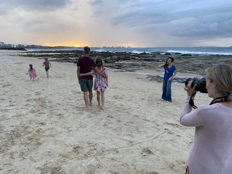 A family walking on the beach while a photographer takes shots of them.