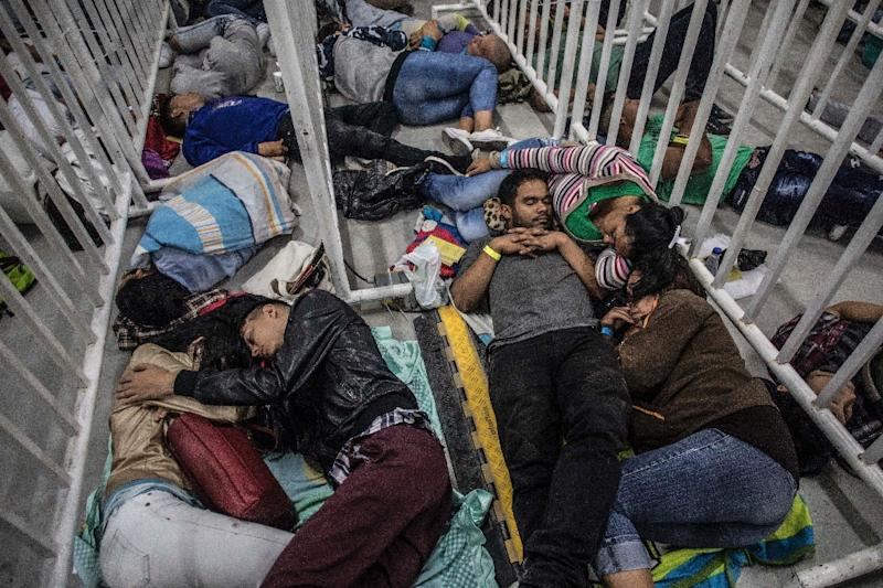 Venezuelan migrants sleep in a street as they wait to sign up for a work program in Medellin, Colombia, on September 27, 2018. (AFP Photo/JOAQUIN SARMIENTO)