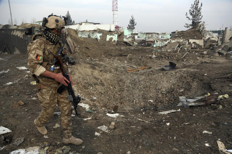 FILE - In this Nov. 29, 2018, file photo a Afghan Security forces member walks next to a crater caused by suicide bomb attack in Kabul, Afghanistan. As the Trump administration pushes for peace in Afghanistan, a new U.S. watchdog report says Afghan security forces are shrinking, gaps in security are growing, and the Taliban are largely holding their own despite a surge in American bombing. (AP Photo/Rahmat Gul, File)