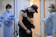In this photo taken on Friday, Jan. 15, 2021 A Romanian gendarme leaves after getting a COVID-19 vaccine at a hospital in Bucharest, Romania. Across the Balkans and the rest of the nations in the southeastern corner of Europe, a vaccination campaign against the coronavirus is overshadowed by heated political debates or conspiracy theories that threaten to thwart the process. In countries like the Czech Republic, Serbia, Bosnia, Romania and Bulgaria, skeptics have ranged from former presidents to top athletes and doctors. Nations that once routinely went through mass inoculations under Communist leaders are deeply split over whether to take the vaccines at all. (AP Photo/Vadim Ghirda)