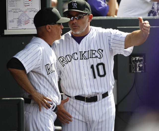 FILE - In this June 15, 2013, file photo, Colorado Rockies hitting coach Dante Bichette, right, confers with bench coach Tom Runnells as the Rockies bat against the Philadelphia Phillies during the fourth inning of a baseball game in Denver. Bichette said on Tuesday, Sept. 24, 2013, the he decided against returning for another season. (AP Photo/David Zalubowski File)