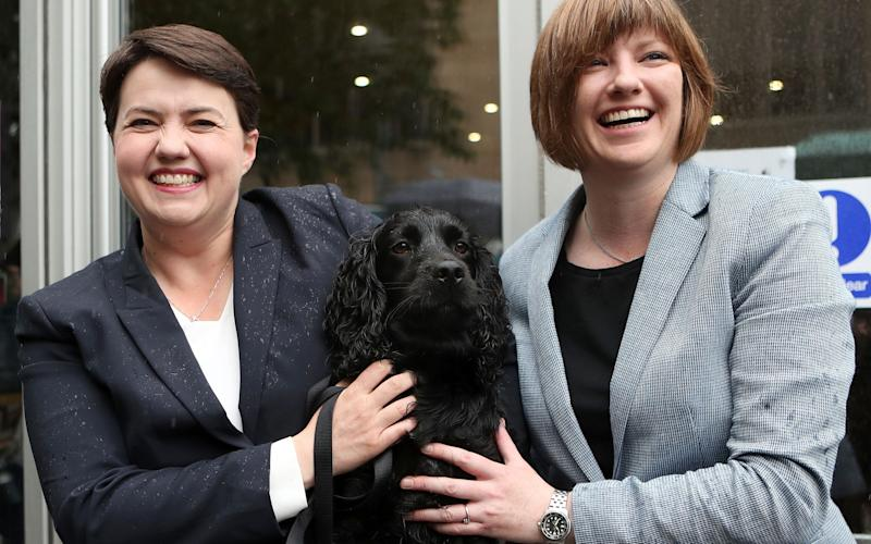 Scottish Conservative leader, Ruth Davidson (L), poses with her partner Jen Wilson and their dog Mister Wilson - AFP