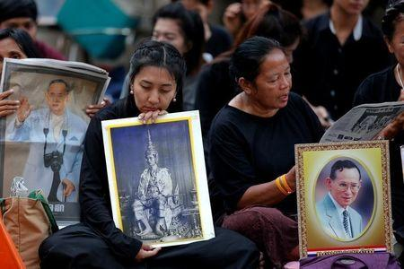 People hold portraits of Thailand's late King Bhumibol Adulyadej at the Siriraj hospital in Bangkok, Thailand, October 14, 2016. REUTERS/Chaiwat Subprasom