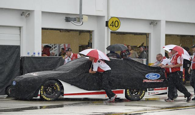 Crew members push Trevor Bayne's car through the garage area prior to the NASCAR Sprint cup Series auto race at Daytona International Speedway in Daytona Beach, Fla., Saturday, July 5, 2014. (AP Photo/Phelan M. Ebenhack)