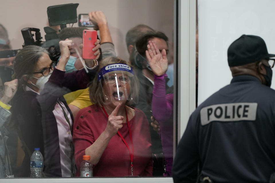 People yell as they look through the windows of the central counting board as police were helping to keep others from entering due to overcrowding, Wednesday, Nov. 4, 2020, in Detroit. (AP Photo/Carlos Osorio)