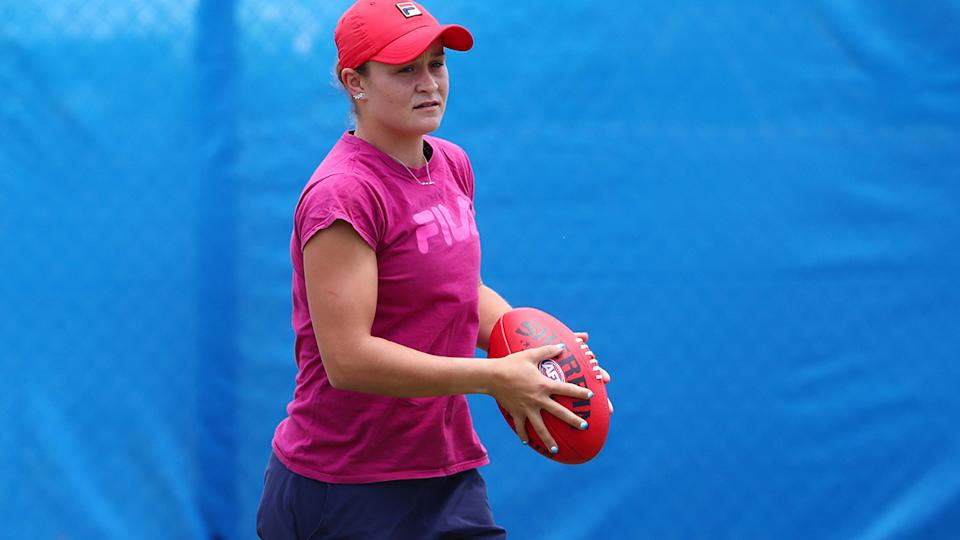 Ashleigh Barty, pictured here warming up with an AFL ball before a tennis match.