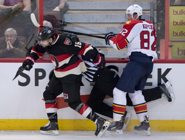 Ottawa Senators left wing Clarke MacArthur, left, and Florida Panthers left wing Tomas Kopecky, right, collide with linesman Brad Kovachik during second-period NHL hockey game action on Thursday, Dec. 19, 2013, in Ottawa, Ontario. (AP Photo/The Canadian Press, Adrian Wyld)