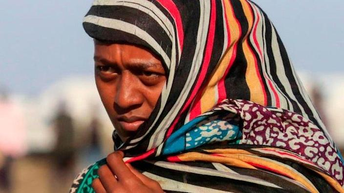 An Ethiopian refugee, who fled the Tigray conflict, walks in the Tenedba camp in Mafaza, eastern Sudan on January 8, 2021, after being transported from the reception centre
