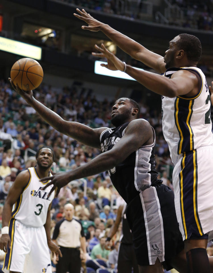 San Antonio Spurs forward DeJuan Blair, left, takes a shot while defended by Utah Jazz center Al Jefferson during the first half of an NBA basketball game Monday, April 9, 2012, in Salt Lake City. (AP Photo/Jim Urquhart)