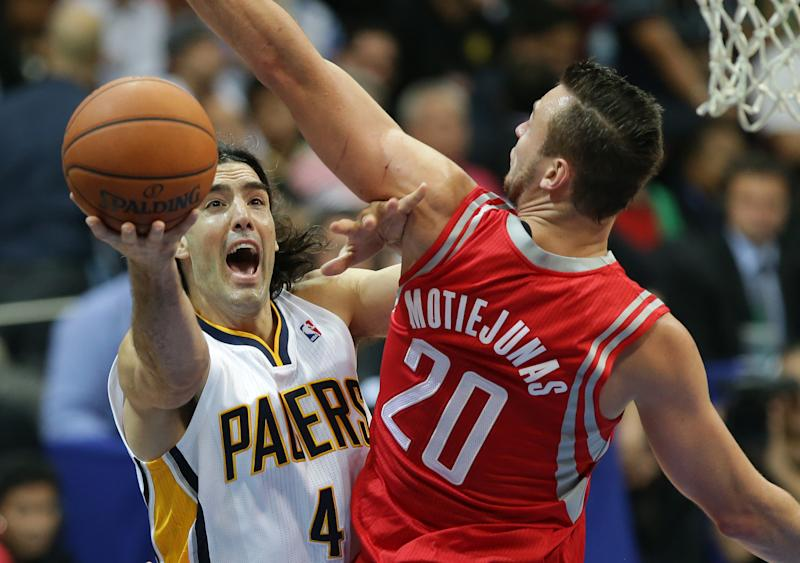 Luis Scola, left, of Indiana Pacers drives past Houston Rockets Donatas Motiejunas, 20, during their preseason game in Pasay, south of Manila, Philippines on Thursday, Oct. 10, 2013. Houston Rockets beat the Indiana Pacers 116-96 during first NBA preseason game in the Philippines.(AP Photo/Aaron Favila)