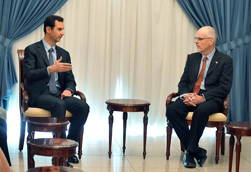In this photo released by the Syrian official news agency SANA, Syrian President Bashar Assad, left, meets with Australian professor Tim Anderson, and a delegation including academics, researchers, and activists in Damascus, Syria, Monday, Dec. 23, 2013. (AP Photo/SANA)
