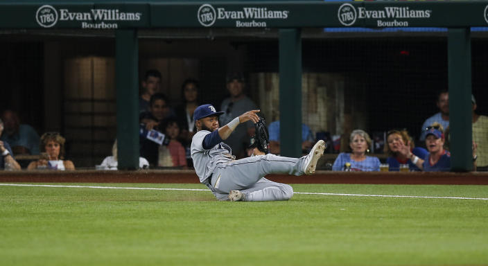 Tampa Bay Rays right fielder Manuel Margot makes a sliding catch of a flyout hit by Texas Rangers' Khris Davis during the fourth inning of a baseball game, Saturday, June 5, 2021, in Arlington, Texas. (AP Photo/Brandon Wade)