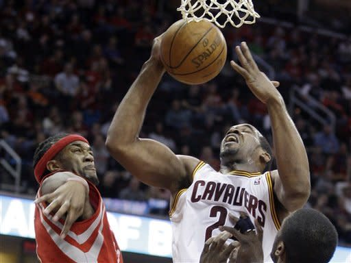 Houston Rockets' Jordan Hill, left, knocks the ball loose from Cleveland Cavaliers' Samardo Samuels in the second quarter in an NBA basketball game Sunday, March 11, 2012, in Cleveland. (AP Photo/Tony Dejak)