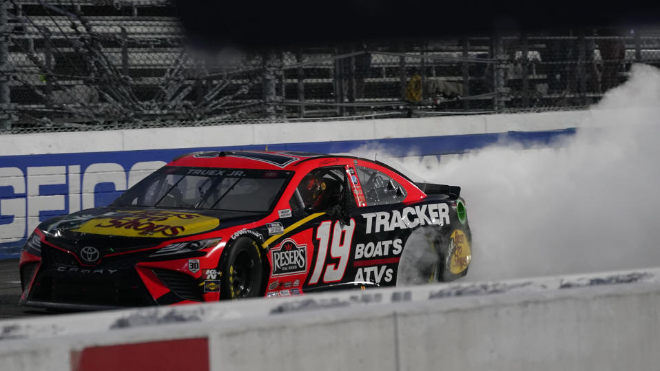 Martin Truex Jr. (19) does a burnout as he celebrates after winning a NASCAR Cup Series auto race at Martinsville Speedway in Martinsville, Va., Sunday, April 11, 2021. (AP Photo/Steve Helber)