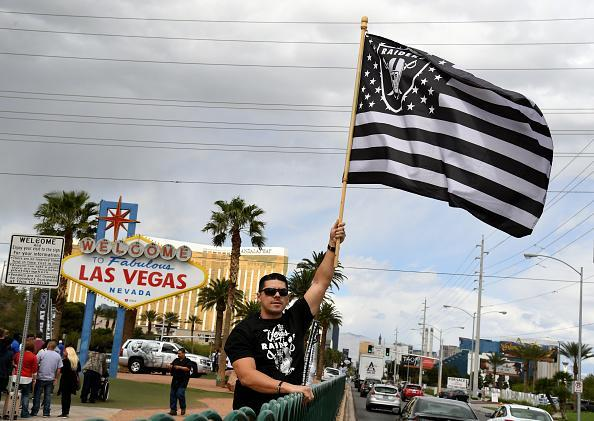 LAS VEGAS, NV - MARCH 27: Oakland Raiders fan Matt Gutierrez of Nevada waves a Raiders flag in front of the Welcome to Fabulous Las Vegas sign after National Football League owners voted 31-1 to approve the team's application to relocate to Las Vegas during their annual meeting on March 27, 2017 in Las Vegas, Nevada. The Raiders are expected to begin play no later than 2020 in a planned 65,000-seat domed stadium to be built in Las Vegas at a cost of about USD 1.9 billion. (Photo by Ethan Miller/Getty Images)