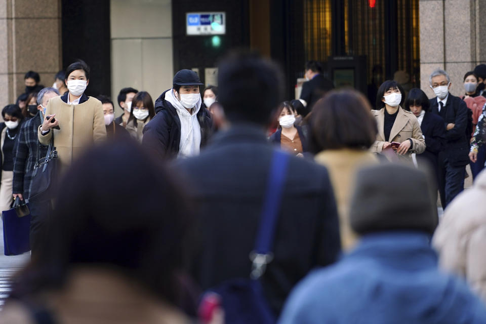 People wearing protective masks to help curb the spread of the coronavirus walk along a pedestrian crossing Thursday, Feb. 25, 2021, in Tokyo. The Japanese capital confirmed more than 340 new coronavirus cases on Thursday. (AP Photo/Eugene Hoshiko)