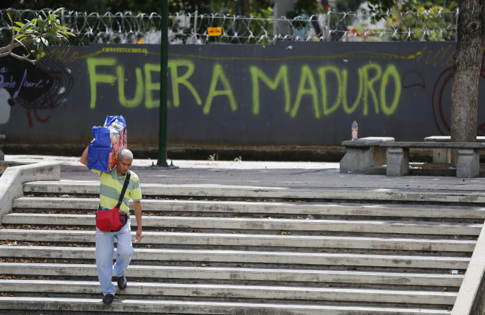 """A man walks past graffiti on the wall of a vacant lot that reads in Spanish: """"Get out Maduro,"""" referring to President Nicolas Maduro in Caracas, Venezuela, Thursday, Jan. 24, 2019. Venezuelans headed into uncharted political waters Thursday, with the young leader of a newly united and combative opposition claiming to hold the presidency and Maduro digging in for a fight with the Trump administration. (AP Photo/Fernando Llano)"""
