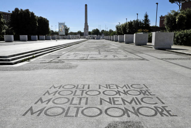 """A Fascist motto reading in Italian """"Many enemies, much honor"""", decorates the mosaic pavement on the avenue from the Olympic stadium to a fascist-era obelisk, in Rome's Foro Italico sporting ground, Thursday, May, 16, 2019. The Foro Italico, formerly called Foro Mussolini (Mussolini's Forum), was built under Mussolini's regime to bolster Rome's bid for the Olympics in the 1940's. The obelisk was built in 1932. (AP Photo/Gregorio Borgia)"""